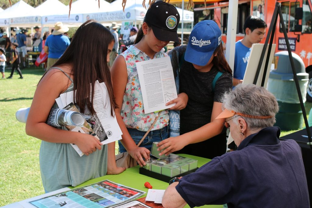 OC volunteer Dillu explains orangutan puzzle to visitors at the 2016 Urban Wildlife Festival